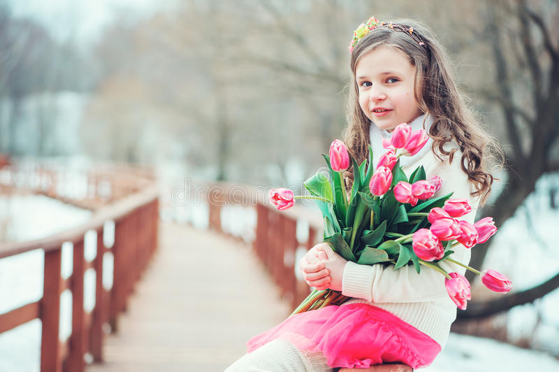 Spring portrait of happy child girl with tulips bouquet on the walk stock images