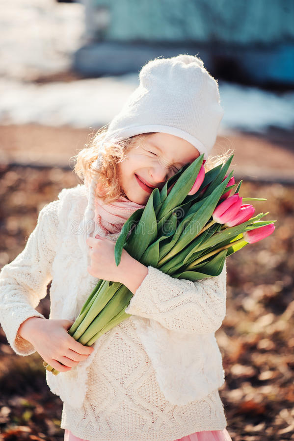 Spring portrait of happy child girl with tulips bouquet for woman's day. Spring portrait of cute happy child girl with tulips bouquet for woman's day stock images