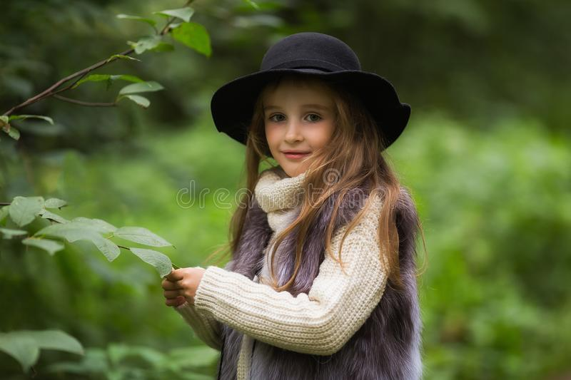 Spring portrait of a little girl.Sweet girl with big brown eyes in a black hat and a fur vest. In the background tree royalty free stock photo