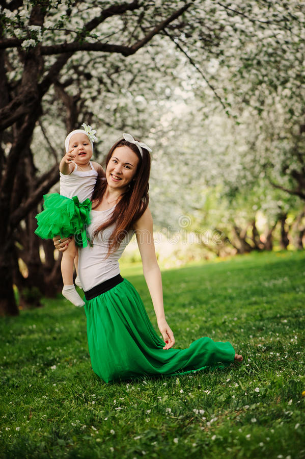 Spring portrait of mother and baby daughter playing outdoor in matching outfit - long skirts and shirts. Happy family enjoyng vacation stock photography
