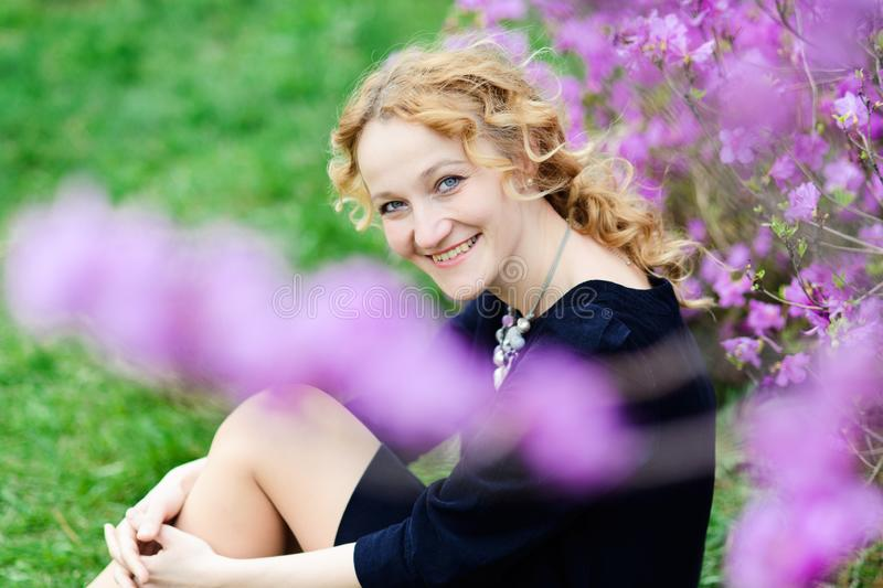 Spring portrait of smiling adult blonde woman, violet flowers royalty free stock images