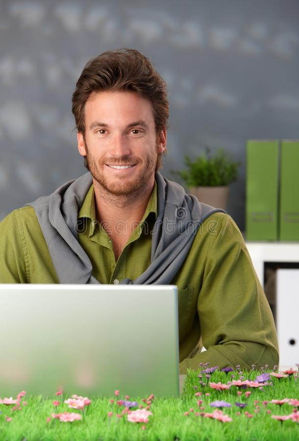 Spring portrait of smiling man with computer. Spring portrait of smiling man sitting in room with laptop computer, looking at camera, table as spring field stock photos