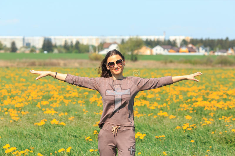 Spring portrait. Young beautiful white girl in a brown sports suit stands in a field of yellow dandelions. stock photos