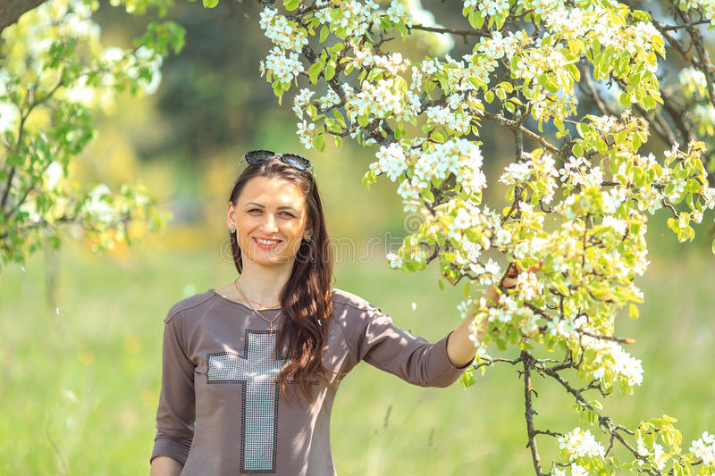 Spring portrait. Young beautiful white girl in a brown sports suit stands near blossoming branches of apple trees in the garden. royalty free stock images