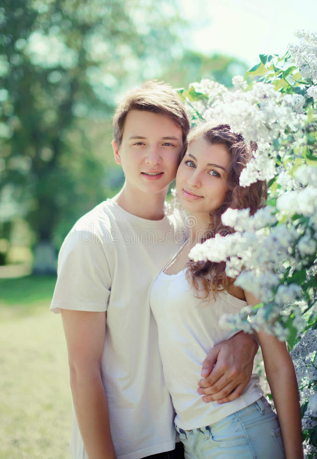 Spring portrait of young couple teenagers in flowering garden royalty free stock photography