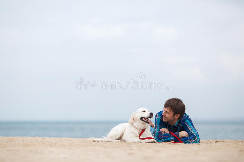 Spring portrait of a young man with a dog on the beach royalty free stock photography