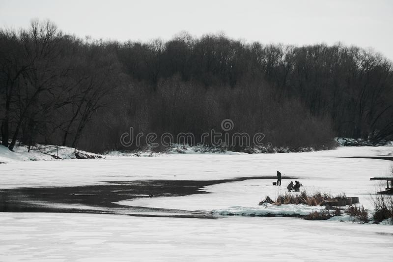 Spring river begins to melt and fishermen on the ice. Partly covered with ice with a tree-covered shore, in cloudy weather, with three fishermen on the ice royalty free stock photos