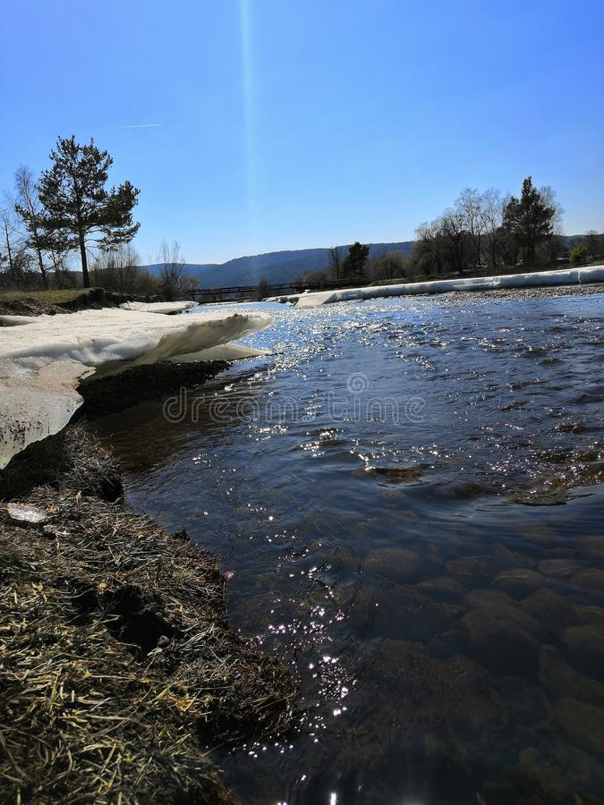 Spring clean fast river with snow-covered banks on a Sunny day. Spring river with clear water, with snow-covered banks, blue sky, on a Sunny day, brilliant water royalty free stock photography