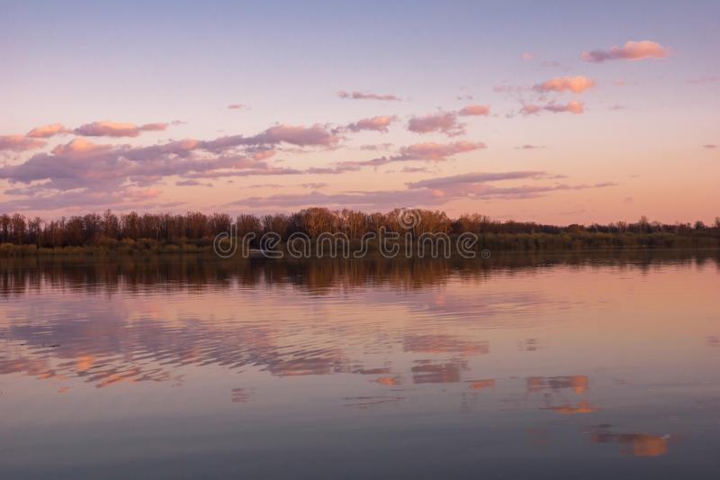 Spring river landscape spill. Evening pink clouds. Wild nature. Color water reflection stock photo