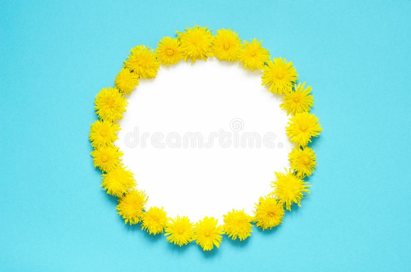 Spring round frame with  dandelion flowers on blue background. stock photography