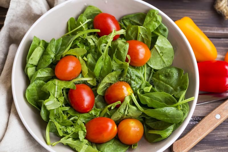 Spring salad closeup with fresh green rocket, spinach leaves and. Cherry tomatoes , top view royalty free stock image