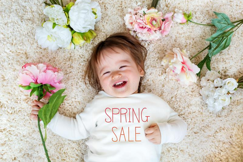 Spring Sale message with happy toddler boy. With spring flowers stock photos