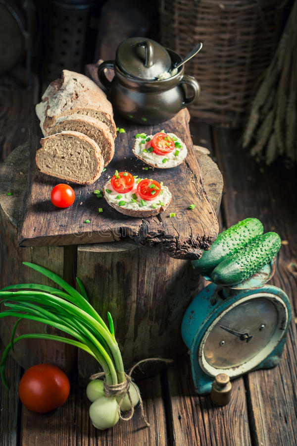 Spring sandwich with fromage cheese, cherry tomatoes and chive. On old wooden board royalty free stock photo