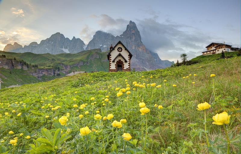 Spring scenery of Dolomites with view of a lovely church at the foothills of rugged mountain peaks. Cimon della Pala  under dramatic dawning sky in Passo Rolle stock image