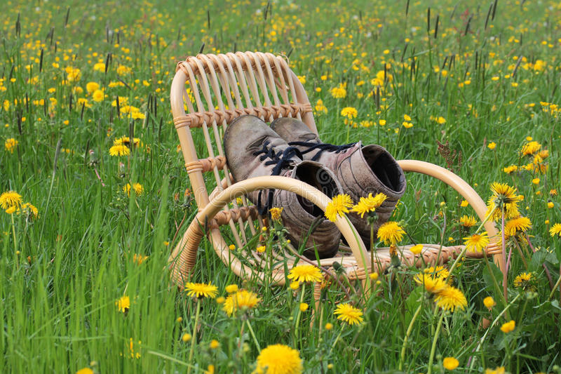 In spring, the season begins mountaineers. Mountain boots on a rocking chair waiting stock image