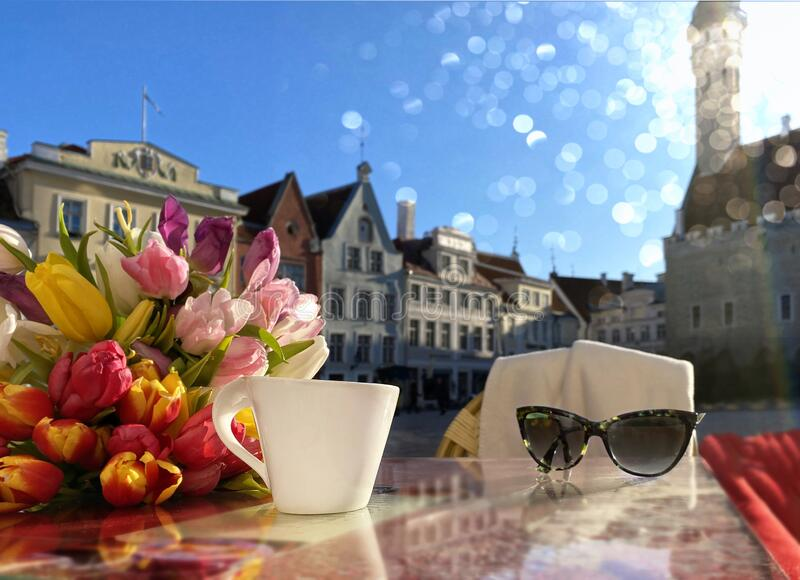 Spring street cafe in Tallinn town square ,cup of coffee on table top and flowers tulip sunlight reflection holiday travel to Esto stock photos