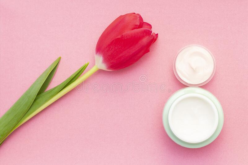 Spring skin care. Tulip and jar of cream on a pink background. Jars of cream in the form of number 8. March 8 royalty free stock photos