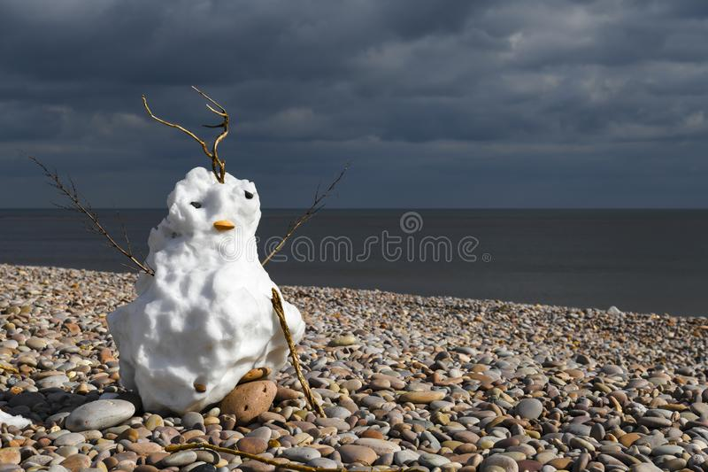 Spring Snowman. A snowman keeping gaurd in the springtime on the beach at Budleigh Salterton in Devon, England. 20 March 2018 royalty free stock photo