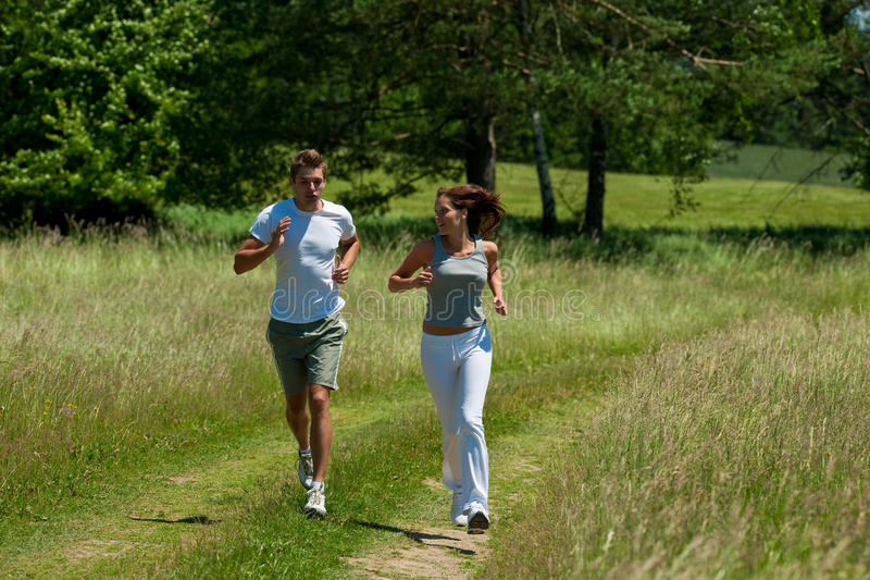Spring - Sportive couple jogging in nature royalty free stock image