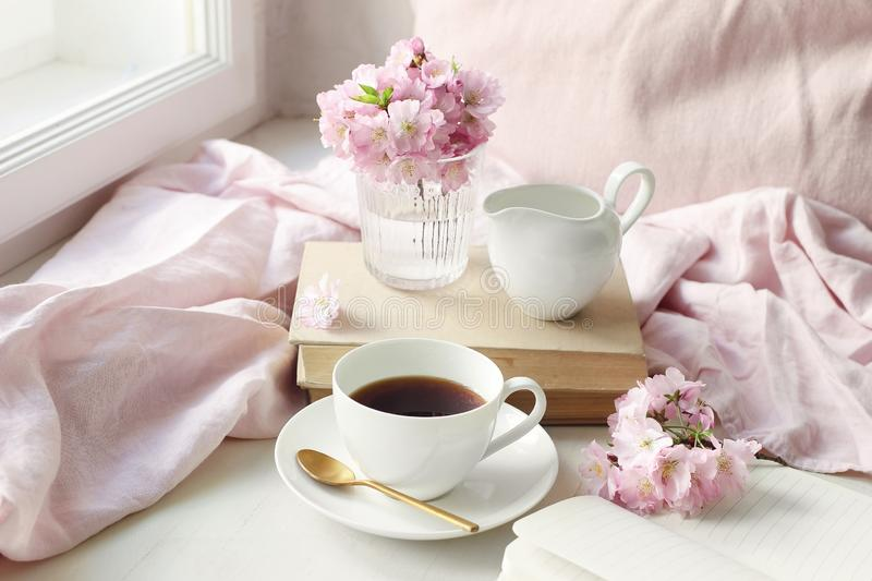 Spring still life scene. Cup of coffee, old books and milk pitcher. Vintage feminine styled photo. Floral composition royalty free stock image