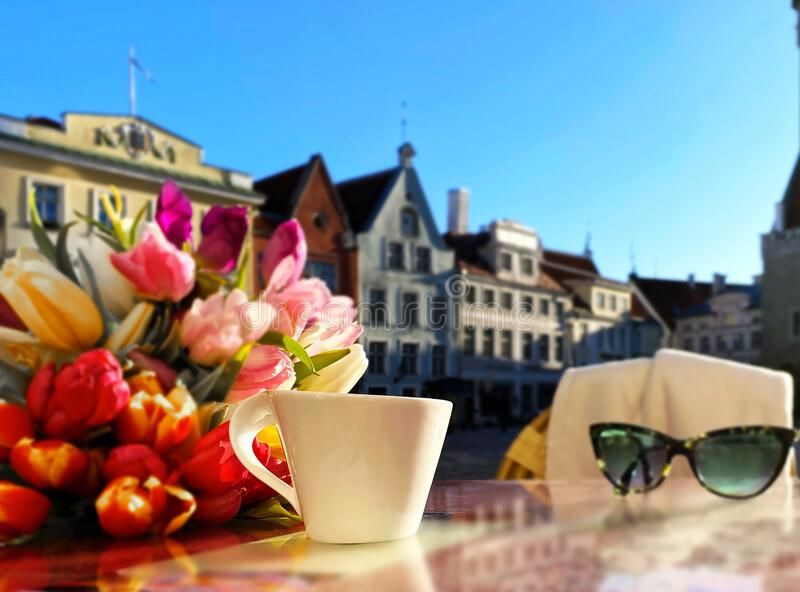 Spring street cafe in Tallinn town square ,cup of coffee on table top and flowers tulip sunlight reflection holiday travel to Esto royalty free stock photo