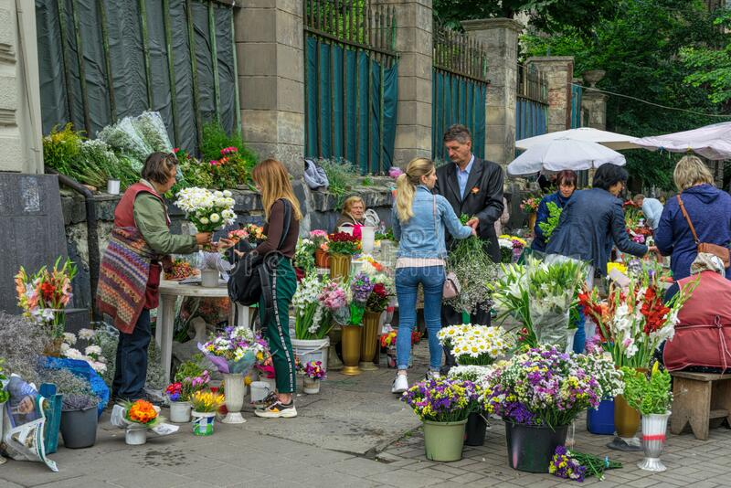 Spring street flower market on the street of Lviv city in Eastern Europe, Ukraine. Lviv, Ukraine - June 25, 2019: Girls buying colorful flower pots with a royalty free stock image