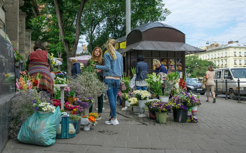 Spring street flower market on the street of Lviv city in Eastern Europe, Ukraine. Lviv, Ukraine - June 25, 2019: Girls buying colorful flower pots with a stock photography