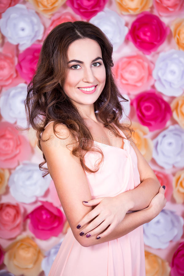 spring and summer concept - portrait of young beautiful woman over colorful flowers wall royalty free stock images