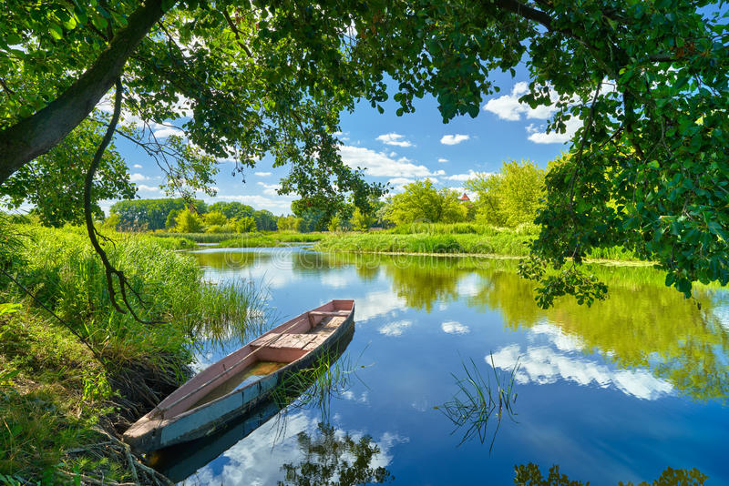 Spring summer landscape blue sky clouds river boat green trees. Spring summer landscape blue sky clouds Narew river boat green trees countryside grass Poland stock images