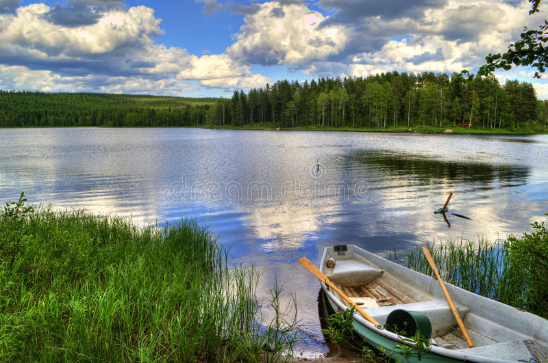 Spring summer landscape blue sky clouds river boat green trees in Sweden. Picturesque village summer landscape in Sweden. The fishing boat on the bank of the royalty free stock photo