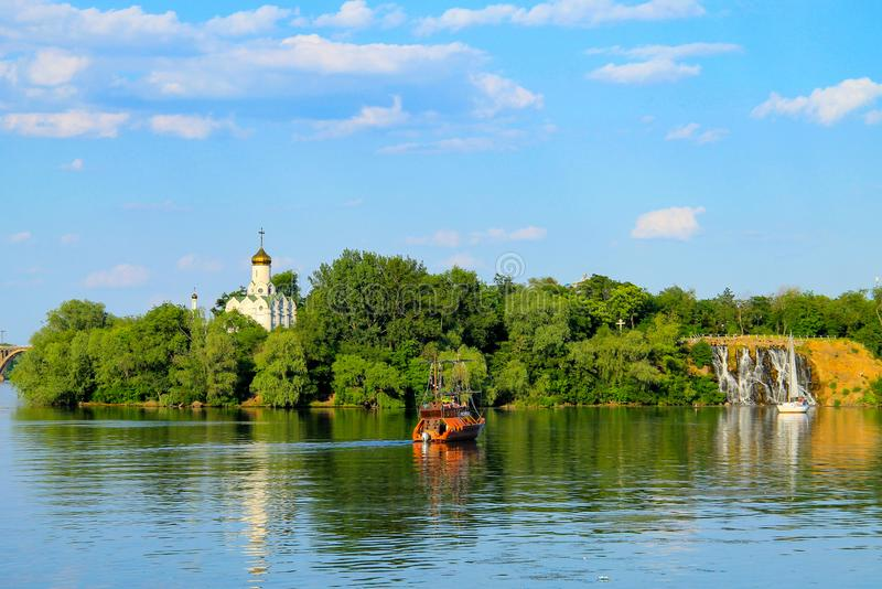 Spring and summer landscape - a green island, a white church and a ship on the river. Monastic island on the Dnieper river. In Dnipro city, Dnepropetrovsk stock image