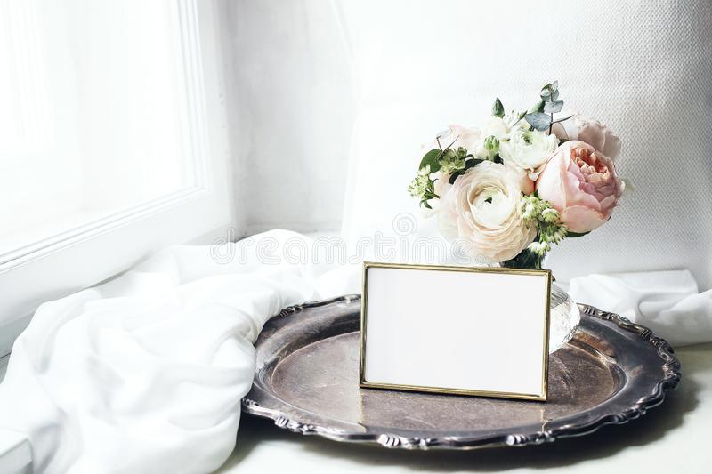 Spring, summer still life. Blank golden photo frame mockup on old silver tray near window. Vintage feminine styled photo. Floral composition of pink English royalty free stock photography