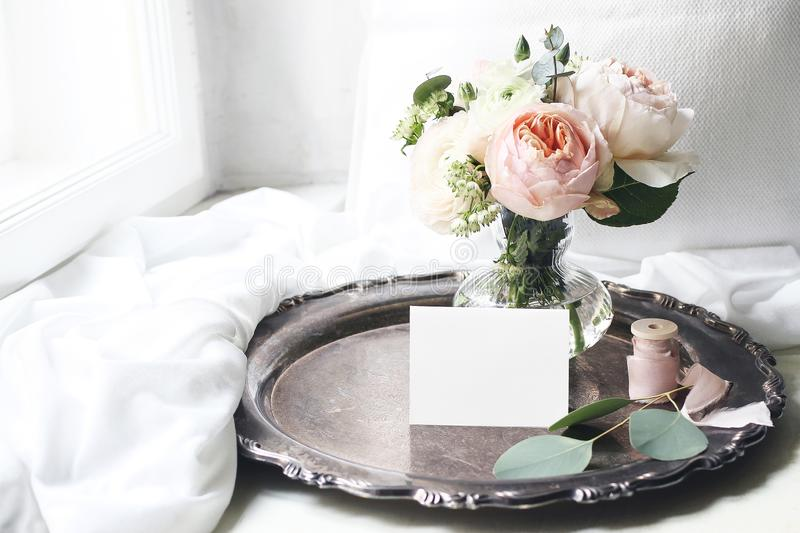 Spring, summer still life scene.Blank place card mockup on old silver tray at windowsill. Vintage wedding feminine. Styled photo, floral composition, bouquet of stock image