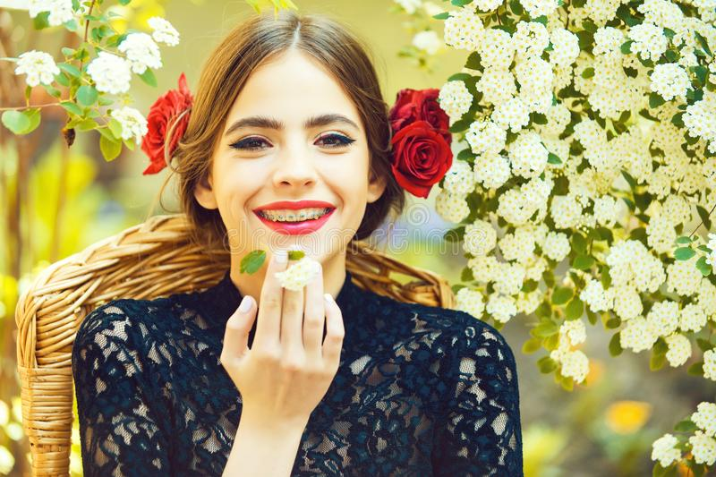 Spring, summer. Stomatology woman smiling with white flower in mouth. Dental braces on teeth, makeup and red roses in brunette hair on sunny day on natural royalty free stock photos