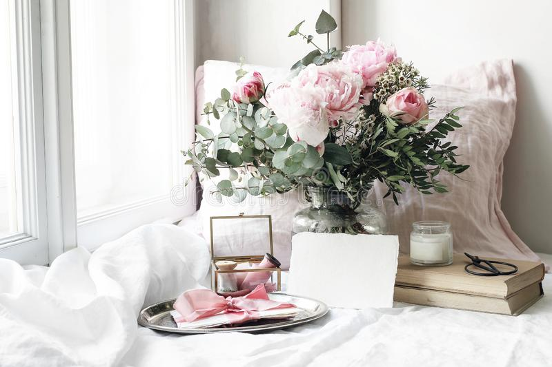 Spring, summer wedding still life scene. Blank paper card mockup, old books and linen pillow at windowsill. Vintage royalty free stock image