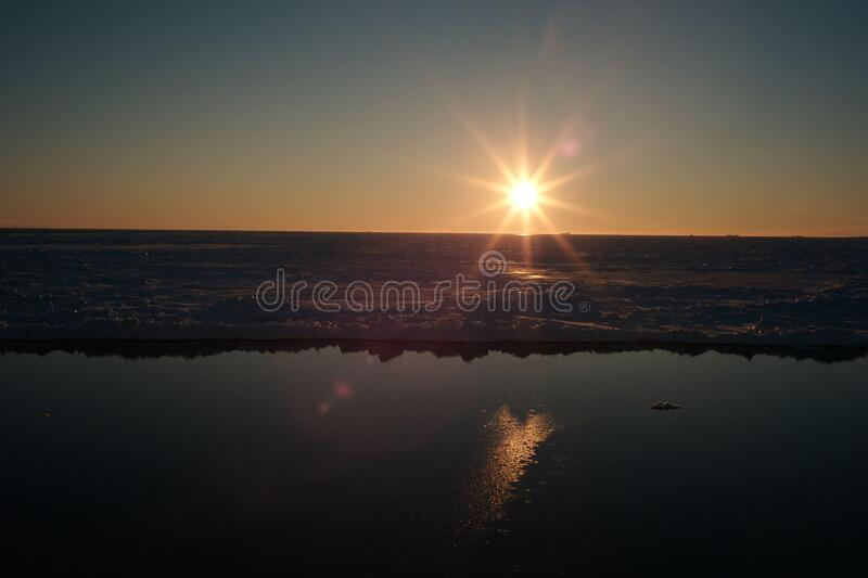 The spring sun sets. Over the edge of the ice stock image