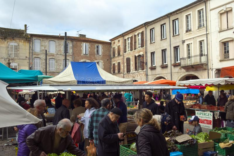 Spring sunshine, Saturday market, Villeneuve-sur-Lot,  France. Villeneuve-sur-Lot, France - 1st April 2017: Shoppers brave a chilly spring morning at the royalty free stock image