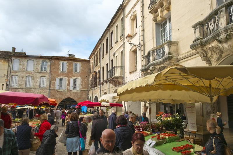 Spring sunshine, Saturday market, Villeneuve-sur-Lot,  France. Villeneuve-sur-Lot, France - 1st April 2017: Shoppers brave a chilly spring morning at the royalty free stock photos