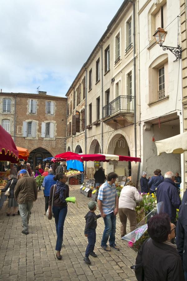 Spring sunshine, Saturday market, Villeneuve-sur-Lot,  France. Villeneuve-sur-Lot, France - 1st April 2017: Shoppers brave a chilly spring morning at the stock photography