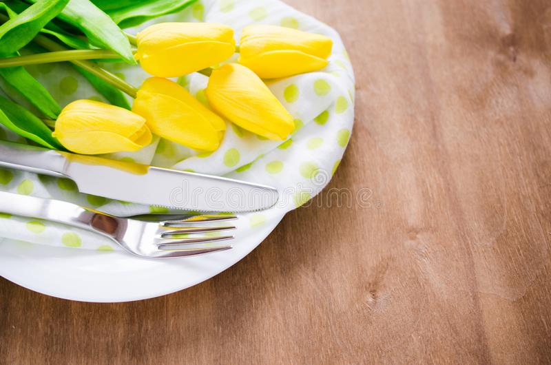 Spring Table Setting for Easter or Mother`s Day. Festive Table Setting in White, Green and Yellow With Tulip. Concept Spring, Easter or Mother`s Day. Selective stock image