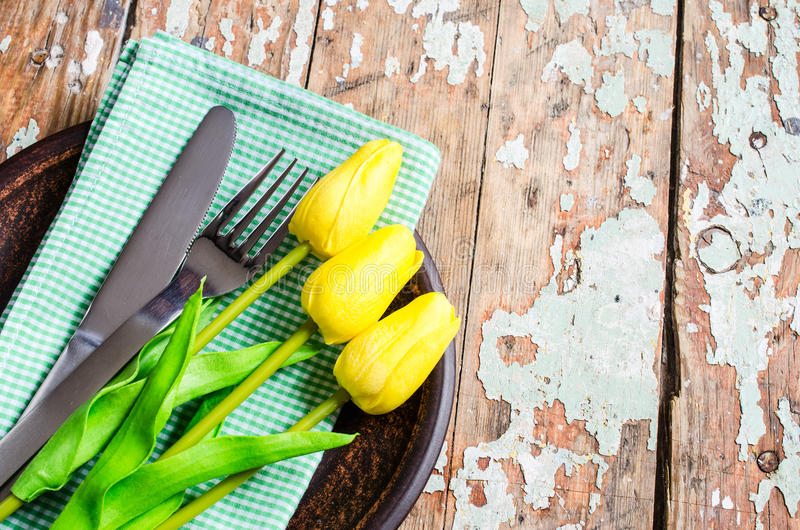 Spring Table Setting for Easter or Mother`s Day. Festive Table Setting in White, Green and Yellow With Tulip. Concept Spring, Easter or Mother`s Day. Selective royalty free stock photos