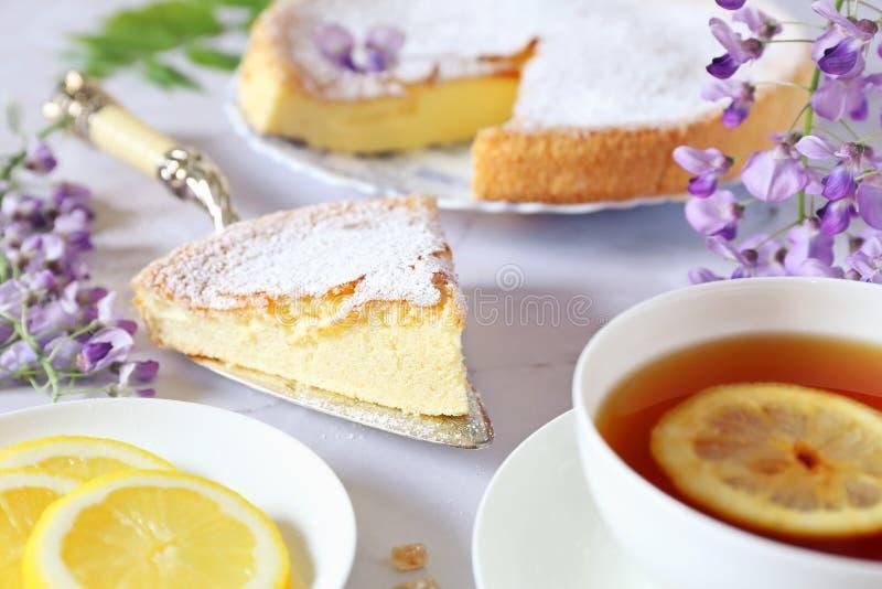 Spring tea-drinking: sponge cake, flowering wisteria and tea royalty free stock photo