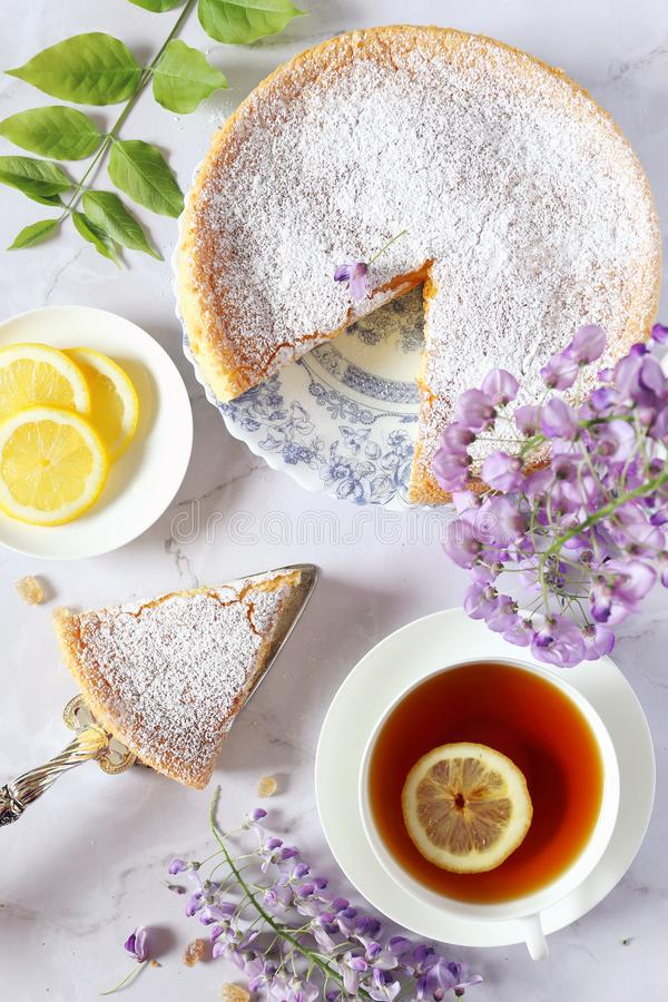 Spring tea with French pastry: sponge cake, flowering wisteria and tea stock photos