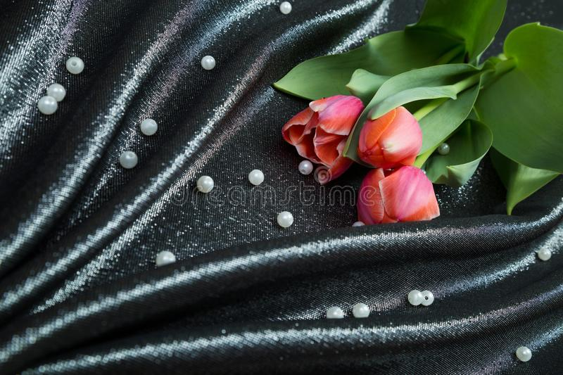 Spring tender pink tulips on brocade fabric stock photography