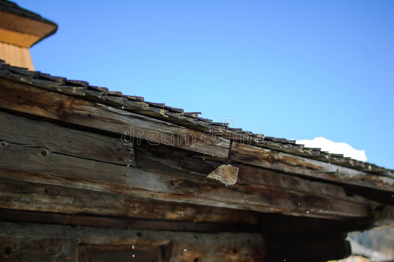 Spring thaw. Drops with old wooden roof. royalty free stock photos