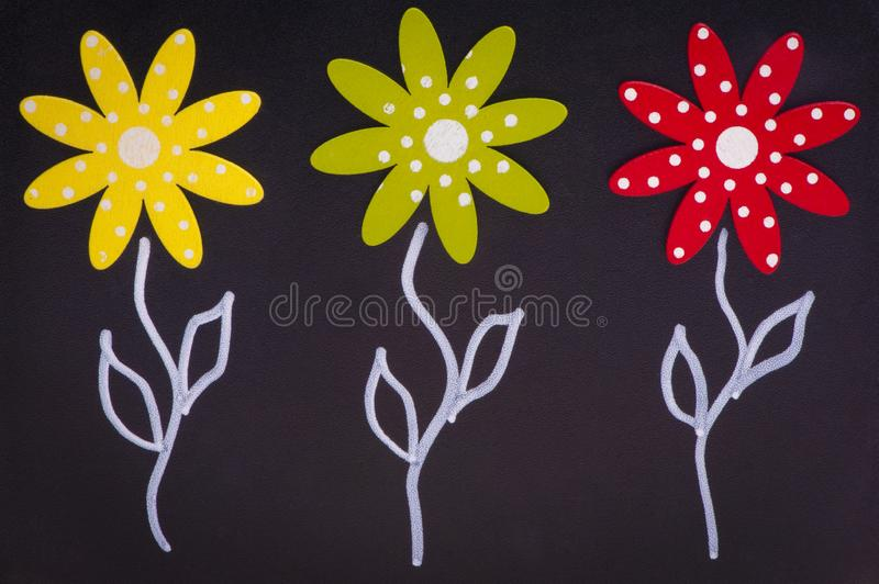 Spring - three flowers on chalkboard - wood material royalty free stock photography
