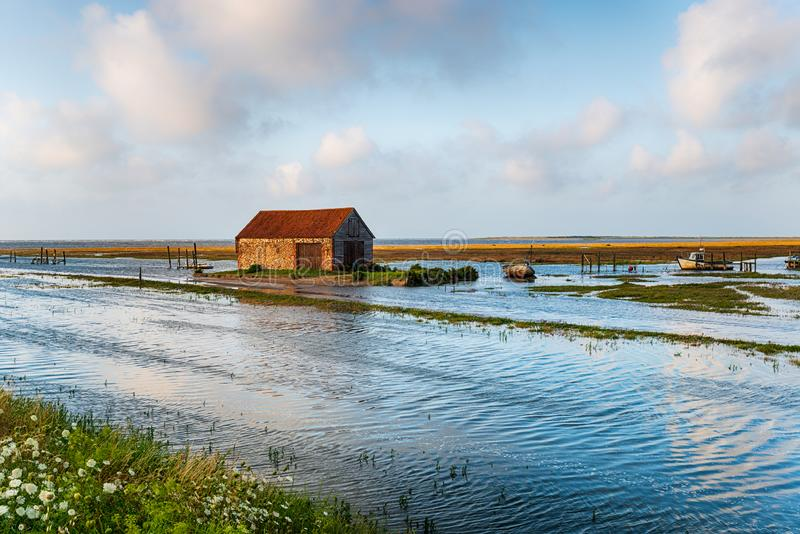 Spring tides flooding the old harbour at Thornham. Spring tides flooding the road at the old harbour at Thornham on the Norfolk coast stock photos