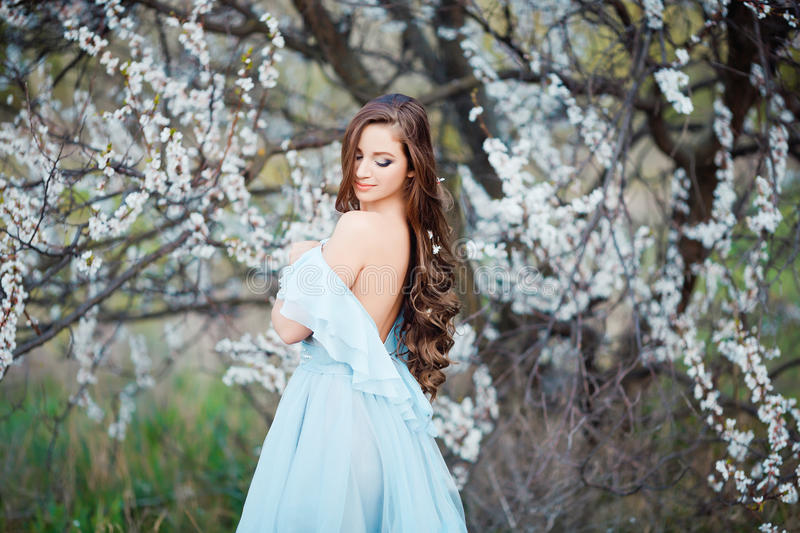 Spring touch. Happy beautiful young woman in blue dress enjoy fresh flowers and sun light in blossom park at sunset. Showing her naked back and shoulder royalty free stock photography