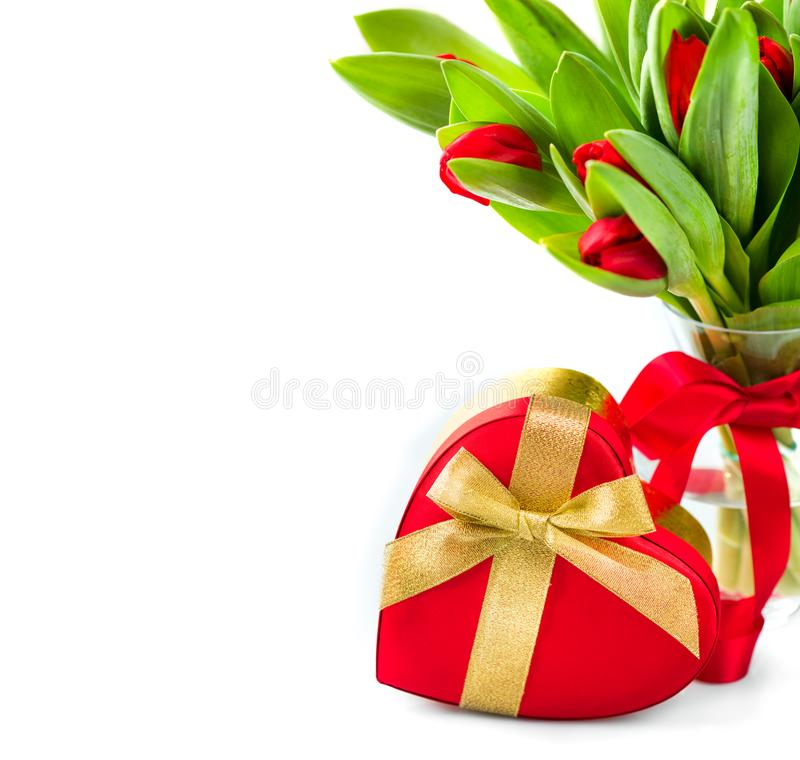 Spring tulip flowers bouquet in a vase over white. Mother`s Day floral border design. Tulips bunch decorated with red satin ribbon stock photos