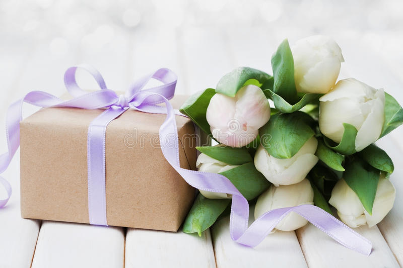 Spring tulip flowers and gift box with bow ribbon on white table. Greeting card for Birthday, Womens or Mothers Day. stock image